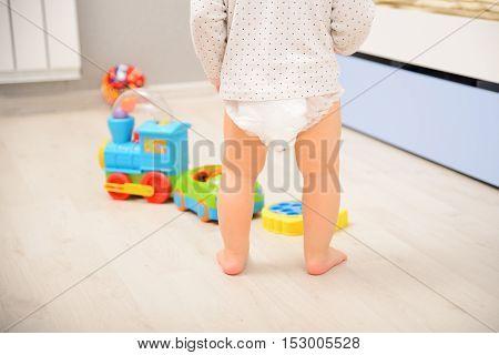 Baby walking on wooden floor in diaper pants. Back view