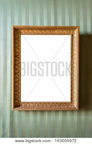 Empty golden picture frame on the green wall