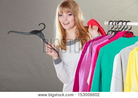 Pretty happy woman with hanger in hand choosing which clothing wear from wardrobe. Young undecided shopper girl bought new clothes. Shopping sale concept.