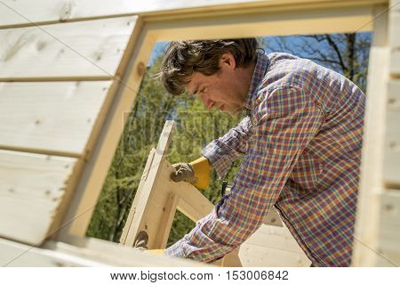 Carpenter or DIY homeowner building a wooden hut outdoors in the garden fitting the window and door frames viewed through a window opening.