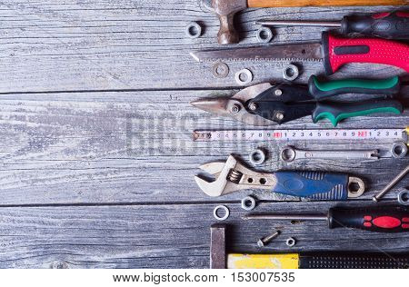 Dirty set of hand old tools on a wooden panel