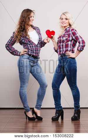 Generation relationship mother's day concept. Adult daughter and mother posing in full length with red heart love symbol. Two cheerful casual style women