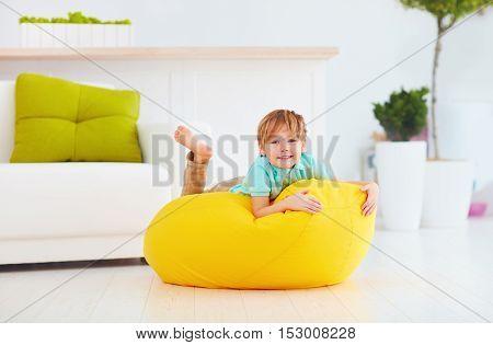 Happy Kid Having Fun On Yellow Bean Bag At Home