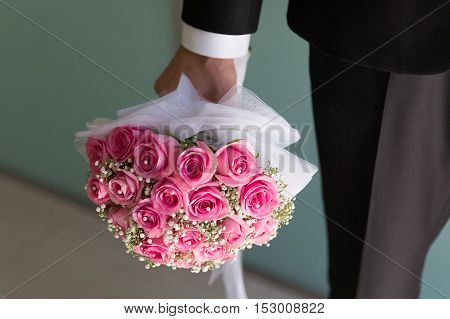 Bride and groom hands holding pink roses bouquet. Closeup
