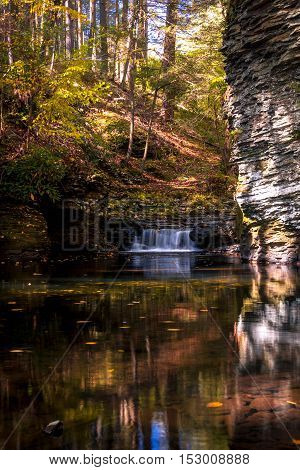 Serene waterfall reflects in the calm water and gorge at Raymondskill Falls near Milford, PA, in fall, portrait