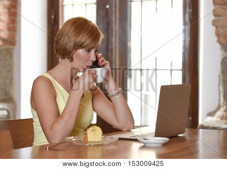 young beautiful and successful woman working busy at coffee shop with laptop computer talking on mobile phone drinking coffee for breakfast connected to wifi cafe internet