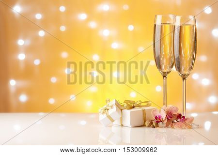 Two glasses with champange, gift boxes and flowers on a yellow background with lights of garland.