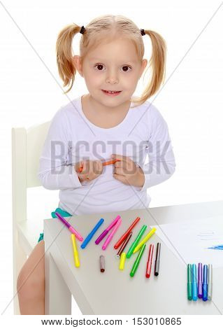 Pretty little blonde girl drawing with markers at the table.Girl holding in hands blue marker.Isolated on white background