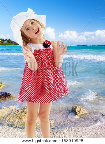 Joyful little girl in a very short polka dot dress and white Panama city beach , claps.Close-up.On the background of white, sandy beaches, blue sky and clouds. The concept of a summer family vacation.