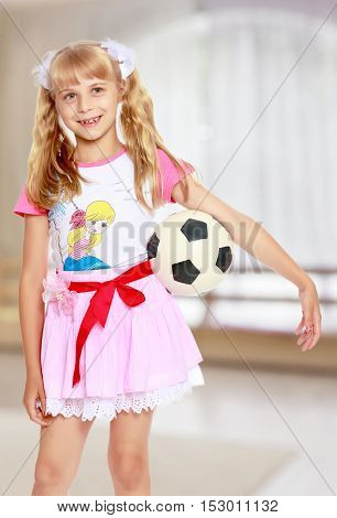 Close-up.Funny little blonde girl in a short pink skirt, holding a hand soccer ball.In a room with a large semi-circular window.