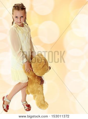 Beautiful little girl in stylish white dress, holding a Teddy bear. Full growth.Brown festive, Christmas background with white snowflakes, circles.