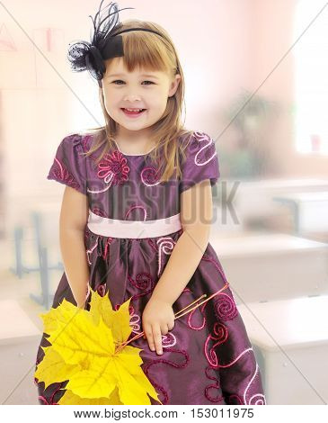 The concept of raising a child in the family, school and kindergarten. In the class where there are school desks. Nice little girl dressed in brown dress. She is holding a bouquet of maple leaves.