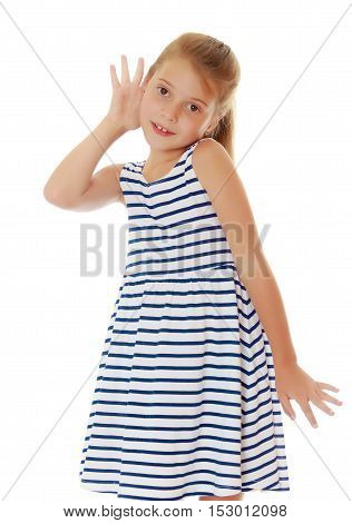 Caucasian little girl in a striped summer dress, listening. Girl holding a hand to his ear.Isolated on white.