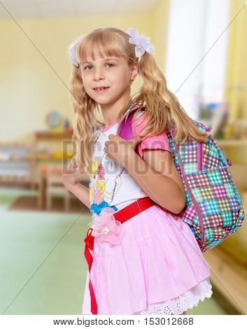 Happy little girl in a pink short skirt with a knapsack on his shoulders. Close-up.In the background children's room where there are shelves with toys.