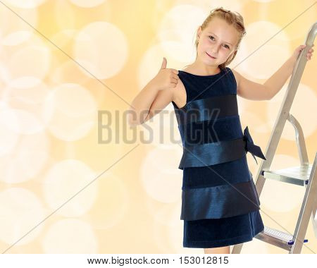 Beautiful little girl dressed in blue dress standing on the ladder and shows thumb.Brown festive, Christmas background with white snowflakes, circles.