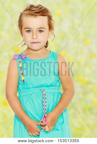 Charming little tanned girl in a blue dress with short sleeves. Close-up.Summer white green blurred background.
