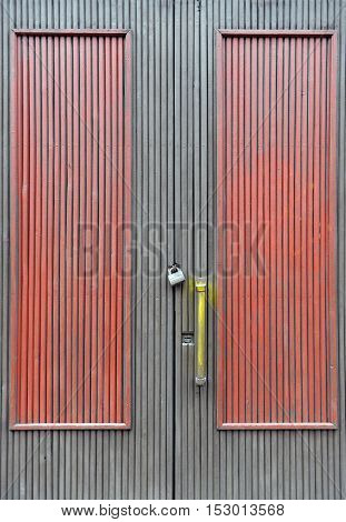 Gray and red old wooden door with two locks and the yellow handle