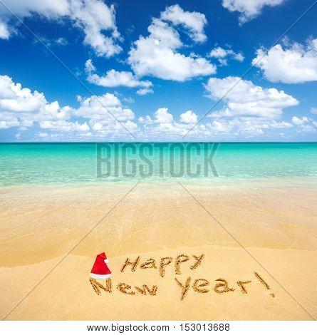 Happy New Year written on a sandy beach