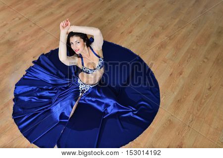 Beautiful woman in arabic costume dancing in motion, oriental or belly dance, shoot from high angle.