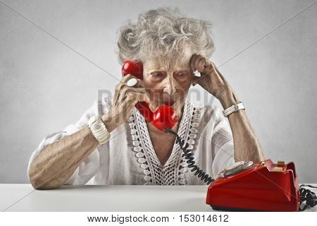 Elderly woman using a red phone