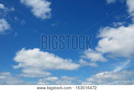 White heap clouds in the blue sky. Cloudscape over horizon. Heaven.