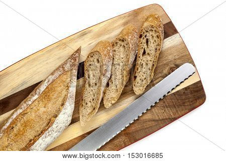 Sliced bread stick on board with knife.  Top view, over white.