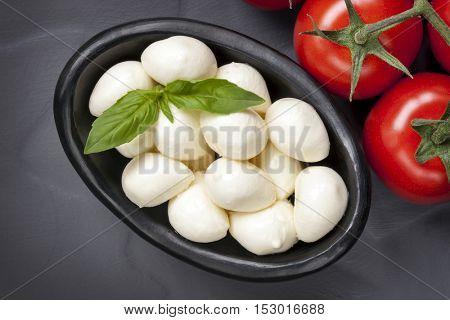 Mozzarella balls, vine tomatoes and basil.  Top view, over dark slate.