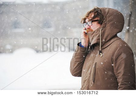 bearded young man standing and using smartphone outdoors in snowy weather in winter