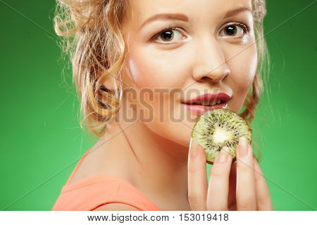 Charming young woman holding fresh juicy kiwi and smiles. Green background.