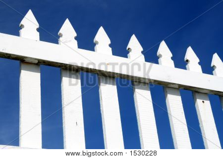 A White Picket Fence And A Dark Blue Sky.