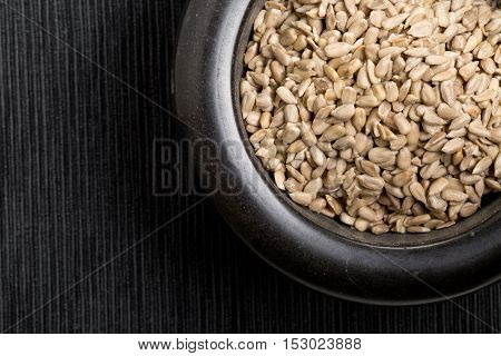 Natural shelled sunflower seeds in black bowl on dark table