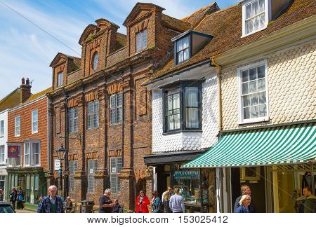 RYE, UK - 1 MAY, 2016: High street of Old Rye town with periodic buildings, lots of people and cars parked on side.