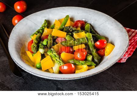 Mediterranean vegetarian salad. Vegan salad with asparagus, cherry tomatoes, yellow bell pepper on gray plate on black slate stone background. Vegetarian or healthy food. Top view