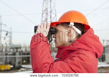 Engineer at Electrical Substation looks through a binoculars. Electrical power industry