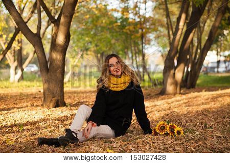 Girl With Sunflowers Sitting In Autumn Leaves
