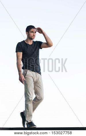 Athletic man in a dark T-shirt looks afar on background of sky. Men's beauty. Street fashion.