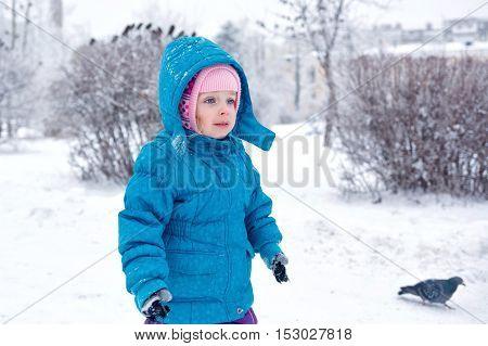 Cute little girl on a walk in a winter park. Kid alone. Childhood Joy.