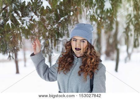 Portrait of pretty attractive girl hipster winter park. Winter fun. Walks in the open air.