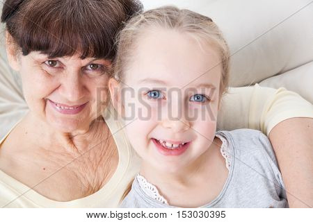 Senior lady with granddaughter happy together in domestic environment