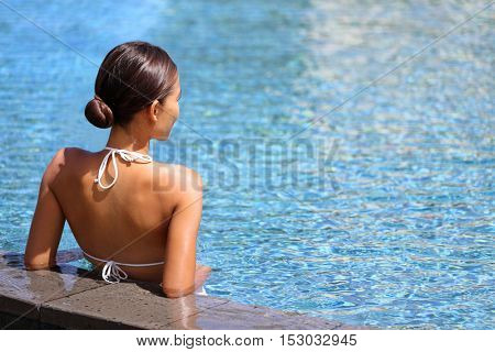 Luxury travel wellness resort bikini woman relaxing in swimming pool. Hydrotherapy spa retreat from behind on side of infinity pool looking away at blue water copyspace. Relaxation vacation concept.