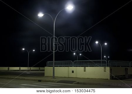Lonely empty carpark at night with no cars and no people around