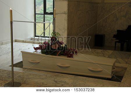 White coffin with funeral flowers in a crematorium