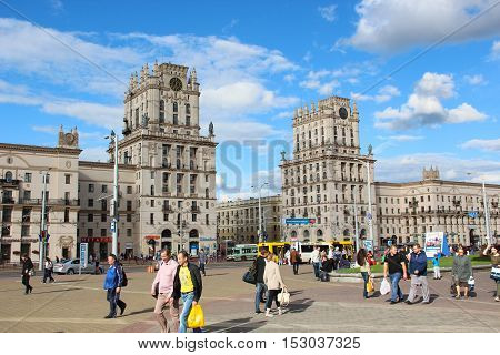 Minsk, Belarus - August 17, 2016: Two towers on Railway station square City Gates. Pedestrians (people, women, men) : tourists and residents go and walk down the street. Sunny summer day.