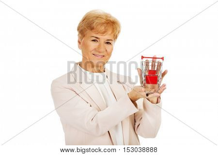 Smile elderly woman holding small trolley