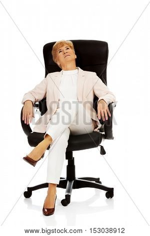 Smile relaxing elderly business woman sitting on armchair