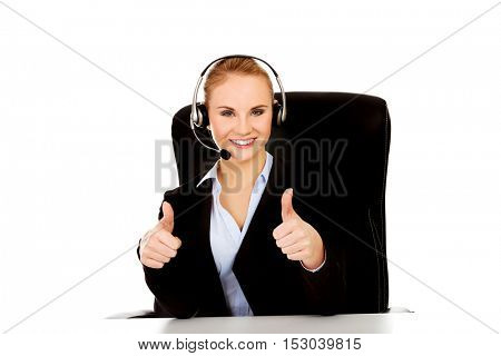 Smiling phone operator in headphones sitting  behind the desk