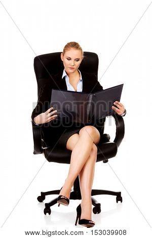 Pensive business woman sitting on armchair and reading notes