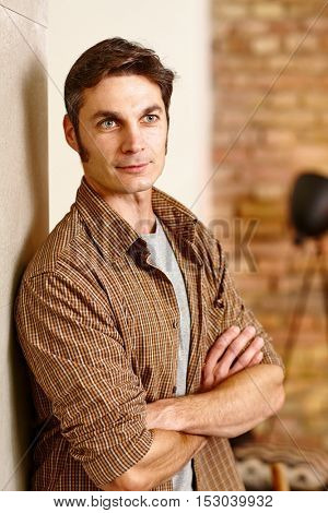 Casual man standing against wall arms crossed, looking away.