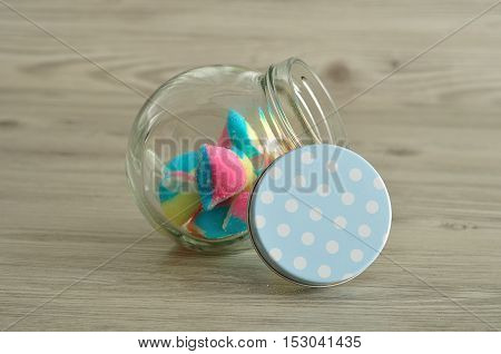 A glass jar with a blue polka dot lid half filled with candy