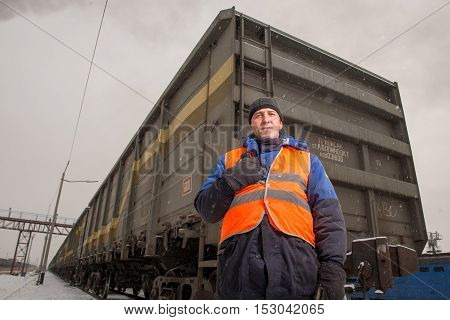 Russia - Oktober, 2016: Rail worker coordinating cargo loading to transport train on the tracks